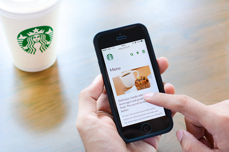 Hand holding smart phone opening online menu web page of Starbucks with Starbucks coffee cup on the table.