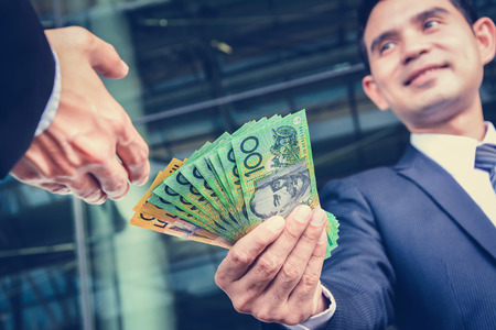 pay money: Businessmen passing money, Australia dollar (AUD) banknotes