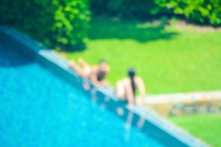 couple outdoor: Blurred image of two people on swimming pool edge beside garden Stock Photo