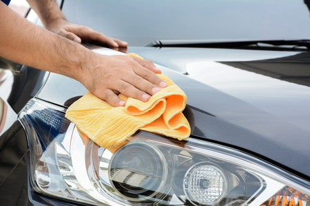 car in garage: A man cleaning car with microfiber cloth, car detailing (or valeting) concept