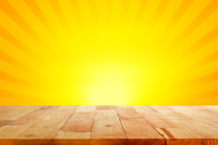 Wood table top on yellow and orange radiate (sunburst) background - can be used for display or montage your products