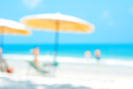 relaxing beach: Blurred beach background with beach umbrellas, and some people - summer holiday background concept