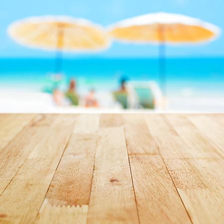 Houten tafelblad op blauwe zee achtergrond met strand parasols en sommige mensen ontspannen op het strand, zomer vakantie achtergrond concept wazig - kan worden gebruikt voor weergave of montage van uw producten