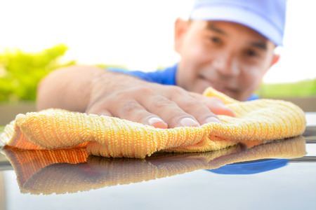 valeting: A man polishing car with microfiber cloth, car detailing (or valeting) concept