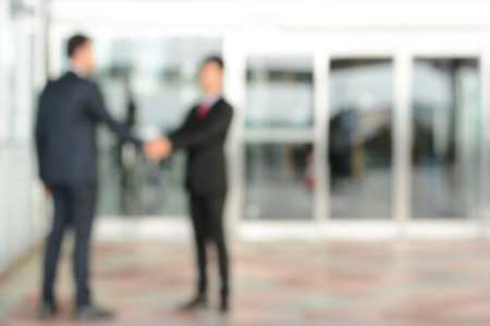 Blurred image of businessmen making handshake in front of office building doors