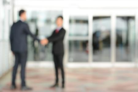 Blurred image of businessmen making handshake in front of office building doors