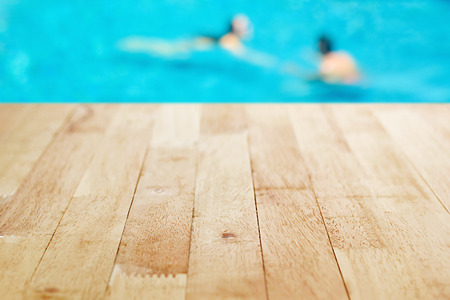 pool tables: Wood table top on blurred background of  swimming pool with few people Stock Photo