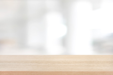 Wood table top on blurred white background of building hallway