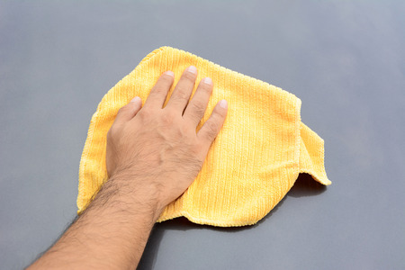cloths: A man polishing car bonnet with microfiber cloth