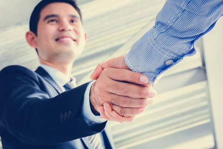 business  deal: Asian businessmen making handshake with smiling face - greeting, dealing, merger and acquisition concepts