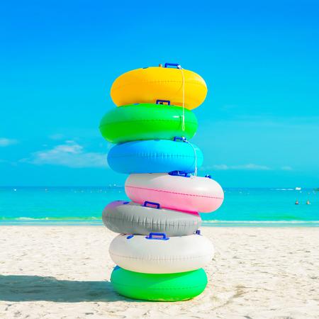 nadar: Pila de anillos de colores de goma (o anillos de natación) en la playa de arena blanca - concepto de vacaciones de verano