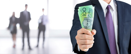 australian dollars: Businessman hand holding money, Australian dollar (AUD) banknotes - financial and investment panorama background