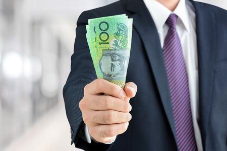 dollaro: Imprenditore mano che tiene i soldi, dollaro australiano banconote (AUD) - finanziario, il successo degli investimenti e concetti di business redditizio