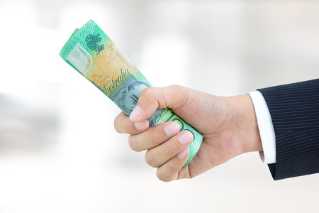 Hand of businessman  giving roll of money, Australian dollar (AUD) banknotes