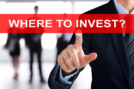 tab: Businessman hand touching WHERE TO INVEST? tab on virtual screen