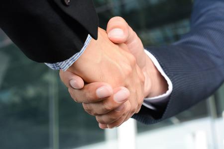 Close-up van zakenman handen maken handdruk - groet, omgaan, fusies en overnames concepten