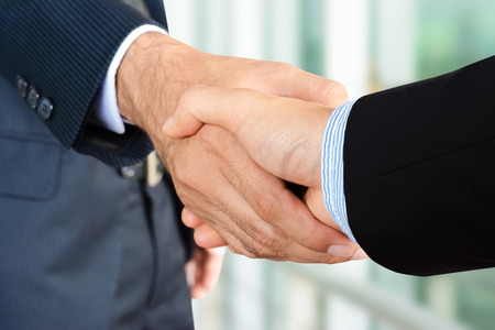handclasp: Close up of businessman hands making handshake - greeting, dealing, merger and acquisition concepts