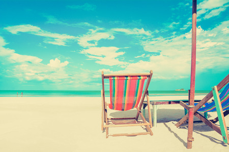 deck chairs: Beach chairs on white sand beach in sunny sky background, vintage tone - summer holiday concept
