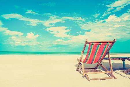 Solstol på vit sandstrand i soliga himmel bakgrund, vintage ton - sommarsemester koncept