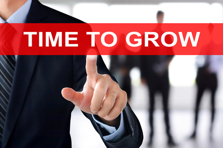 grows: Businessman hand touching TIME TO GROW text on virtual screen