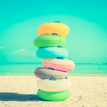 float tube: Stack of colorful rubber rings (or swim rings) on white sand beach, vintange tone - summer holiday concept