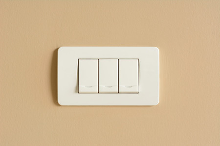 Triple light switches on colored concrete wall