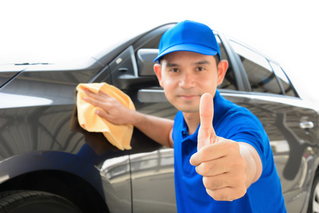 A man giving thumbs up while cleaning car, auto detailing (or valeting) concept