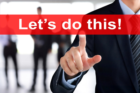 do: Businessman hand touching Lets do this text on virtual screen Stock Photo