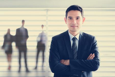 彼の腕を交差しながら笑みを浮かべて若いアジア系のビジネスマン