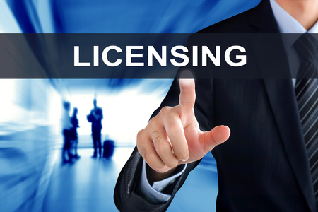 Businessman hand touching LICENSING sign on virtual screen