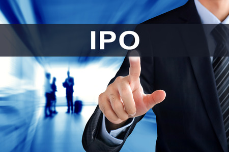 public offering: Businessman hand touching IPO (or Initial Public Offering ) tab on virtual screen