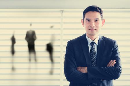 Junge asiatische Geschäftsmann lächelnd, während seine Arme - Führer und Erfolg Geschäftskonzepte Standard-Bild