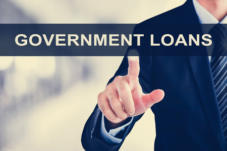 loans: Businessman hand touching GOVERNMENT LOANS sign on virtual screen