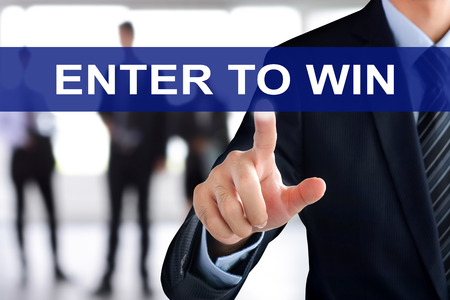 contest: Businessman hand touching ENTER TO WIN tab on virtual screen