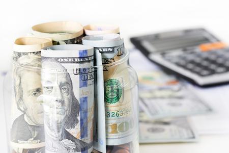 contabilidad: Rollos de dinero, billetes de dólar de los EE.UU., en el frasco de vidrio con la calculadora desenfoque de fondo - financiero, empresarial, la inversión y los conceptos de contabilidad