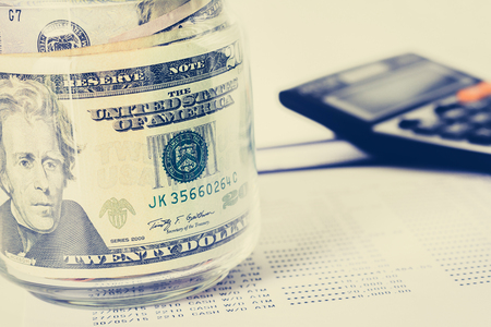 calculadora: El dinero, billetes de dólar de los EE.UU., en el frasco de vidrio con la calculadora desenfoque de fondo - financiero, empresarial, la inversión y los conceptos de contabilidad