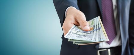dinero: Hombre de negocios dando dinero, estados unidos dólar (USD) proyectos de ley, sobre fondo gris - panorámica del concepto del fondo financiero