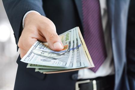 El hombre de negocios dando dinero, Dólar estadounidense (USD) proyectos de ley - conceptos de efectivo, pago y financieros Foto de archivo