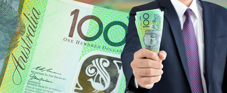 australian dollars: Businessman holding money, Australian dollars (AUD), on 100 banknote background  - financial and investment panorama background concept Stock Photo