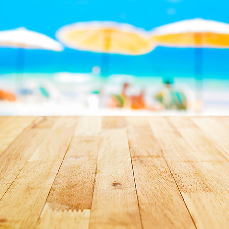 Wood table top on blurred beach background, summer holiday background concept  - can be used for montage or display your products