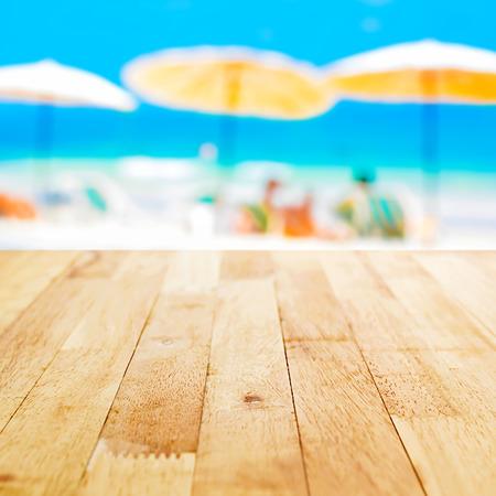 木质桌面上模糊的海滩背景,夏季假期背景概念-可以用来蒙太奇或显示您的产品