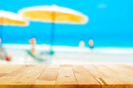 background summer: Wood table top on blurred beach background, summer holiday background concept  - can be used for montage or display your products