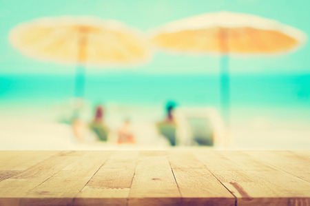 holiday display: Wood table top on blurred beach background, summer holiday background concept, vintage tone  - can be used for montage or display your products Stock Photo