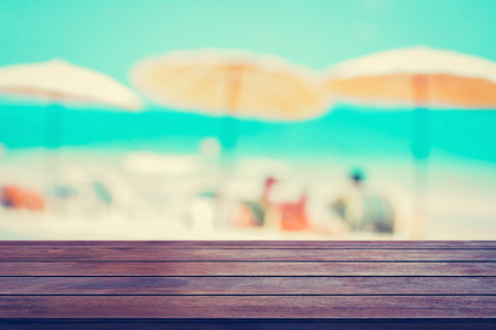 holiday table: Wood table top on blurred beach baackground, summer holiday background concept, vintage tone  - can be used for montage or display your products
