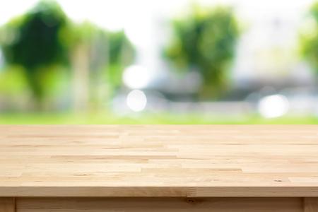 Dřevěný stůl na rozmazaném zeleném pozadí stromu - lze použít k montáži nebo zobrazení vašich produktů