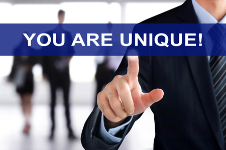 uniquely: Businessman hand touching YOU ARE UNIQUE tab on virtual screen