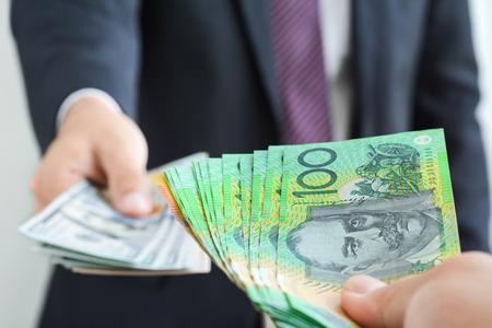 Geld wisselen en trading concept - hand houden Australische dollar (AUD) bankbiljetten op onscherpte achtergrond van zakenman die Amerikaanse dollar (USD) rekeningen, op het punt om te ruilen Stockfoto