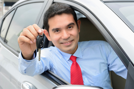 new driver: Smiling asian businessman as a driver showing car key (key focused)