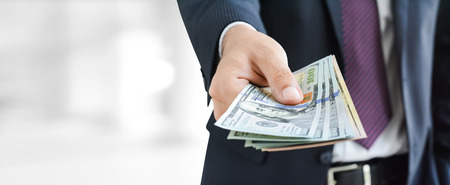 Businessman hands giving money, US dollar bills - business and financial panoramic header background concept