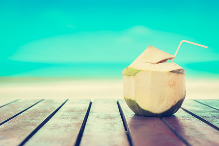 Coconut juice on wood table in blurred beach background, vintage tone Stock Photo